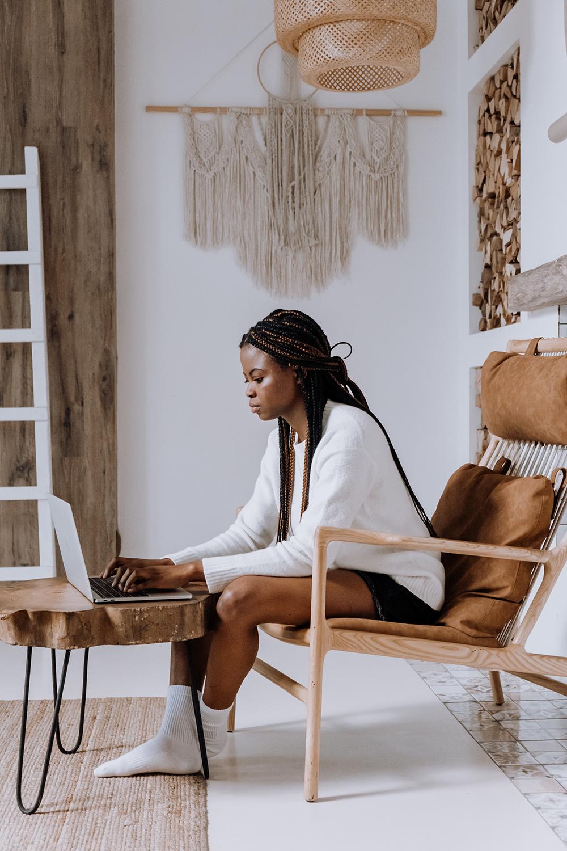 En kvinne som sitter i en god stol med en PC foran seg.