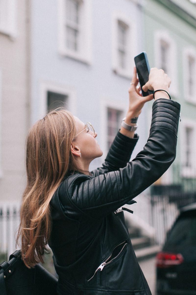 Dame tar bilder i gata med telefonen sin.